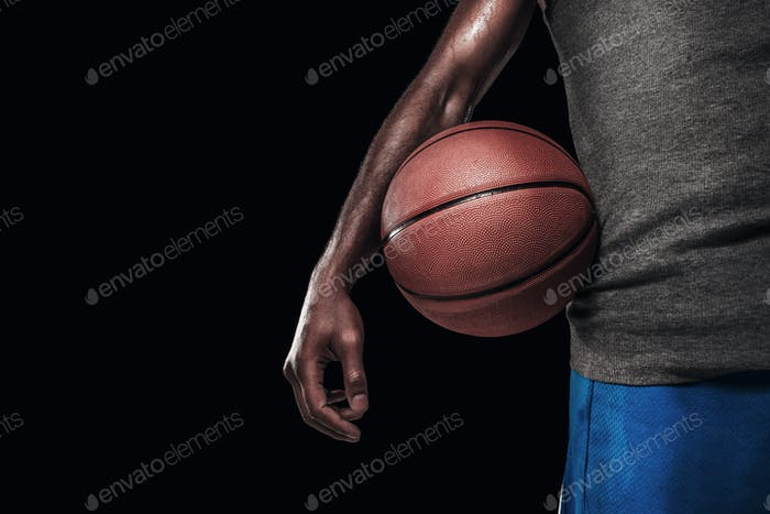 The hands of a basketball player with ball