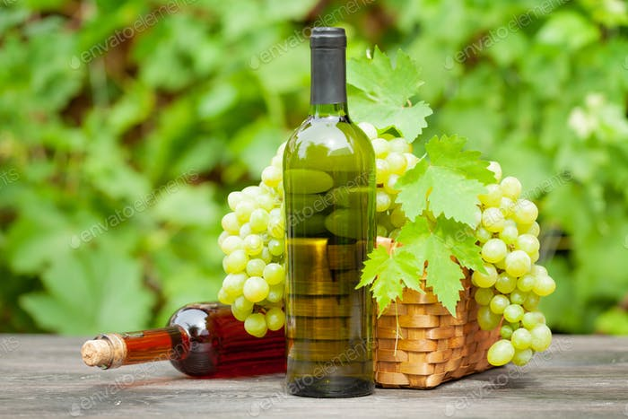 Weiß- und Rosenweinflasche und reife Trauben
