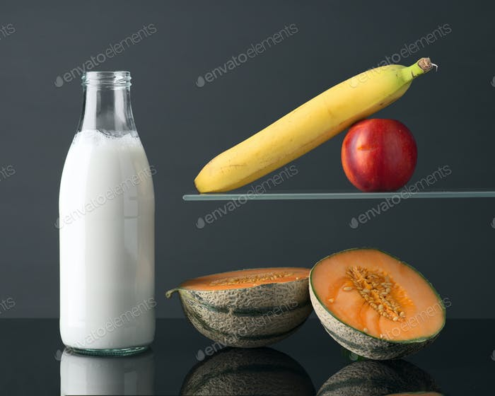 bottle of milk and fruits on gray background