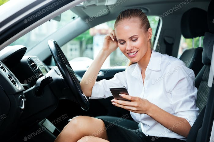 Smiling business woman dialing phone number while sitting in car