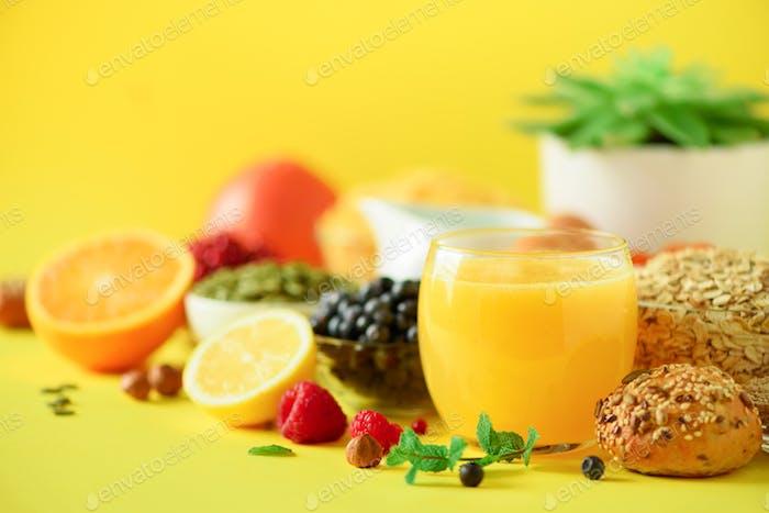 Orange juice, fresh berries, milk, yogurt, boiled egg, nuts, fruits, banana, peach for breakfast on