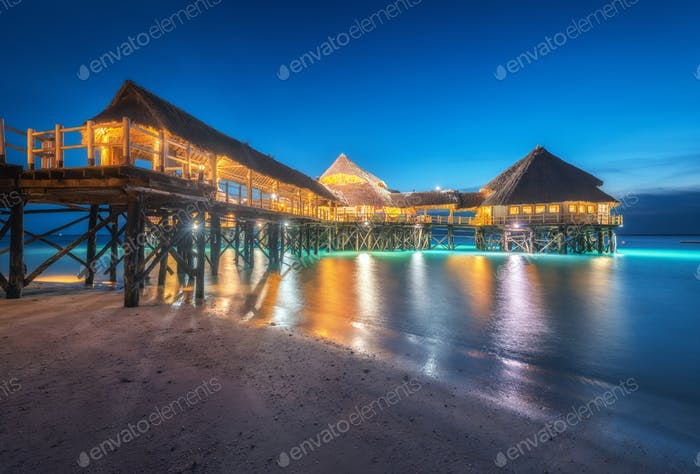 Beautiful wooden restaurant on the water in summer night