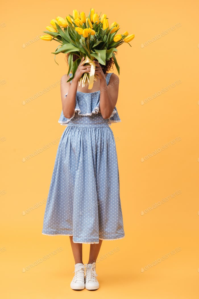 Full-length portrait of african woman hiding behind bouquet flow