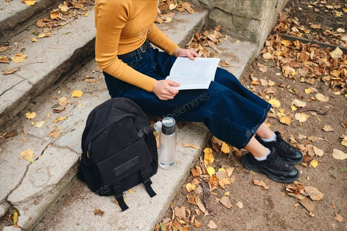 Close up casual student girl reading book on stairs in park