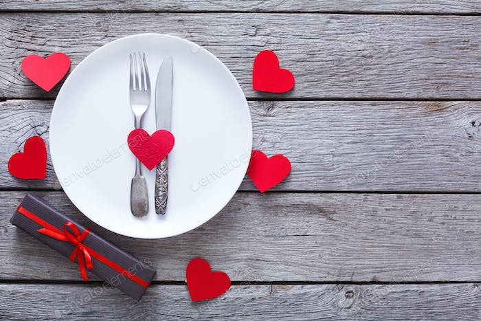 Valentine day or proposal background, cutlery on plate on wood