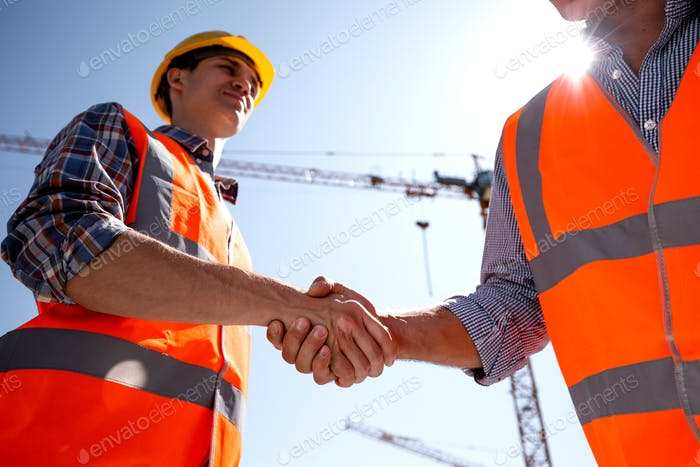 Structural engineer and architect dressed in orange work vests and helmets shake hands on the