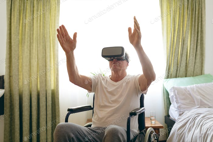Senior male patient using virtual reality headset at retirement home.