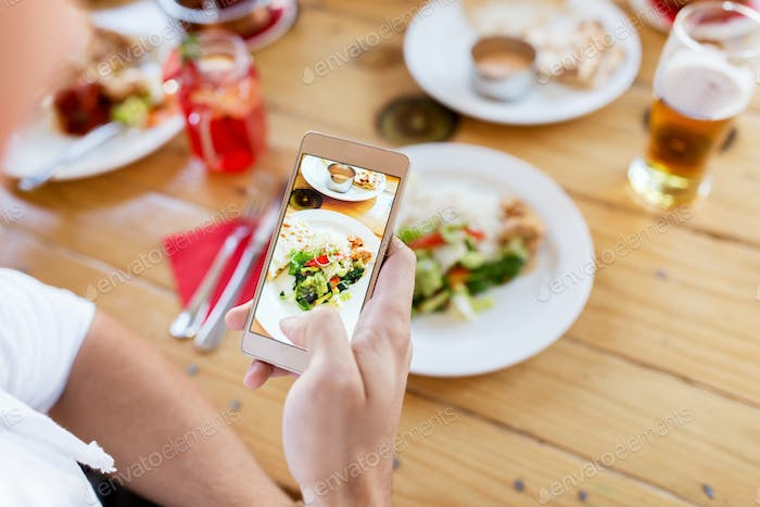 hand with smartphone picturing food at restaurant