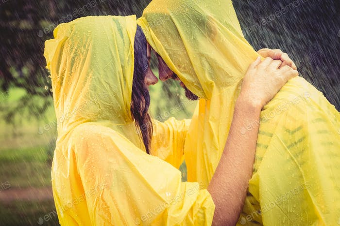 Cute couple wearing protection cape and hugging under the rain in the park
