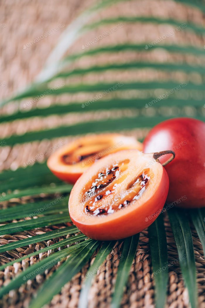 Tamarillo fruit or terong belanda with palm leaves on rattan background. Copy space. Tropical travel