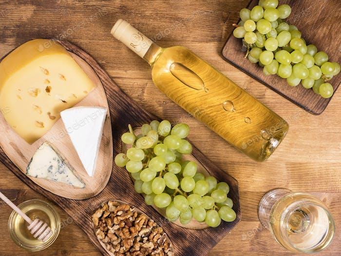 Draufsicht einer Flasche Weißwein neben frischen Trauben auf Holztisch