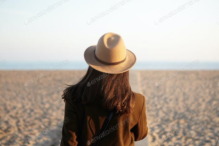 Rear view of young female with loose hair dressed in stylish warm clothing walking down coastline al