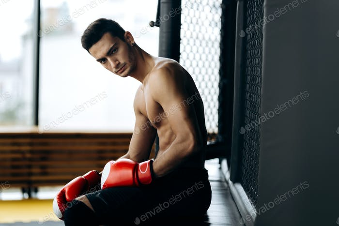 Brutal dark-haired guy with a naked torso and the red boxing gloves on his hands sits on the border