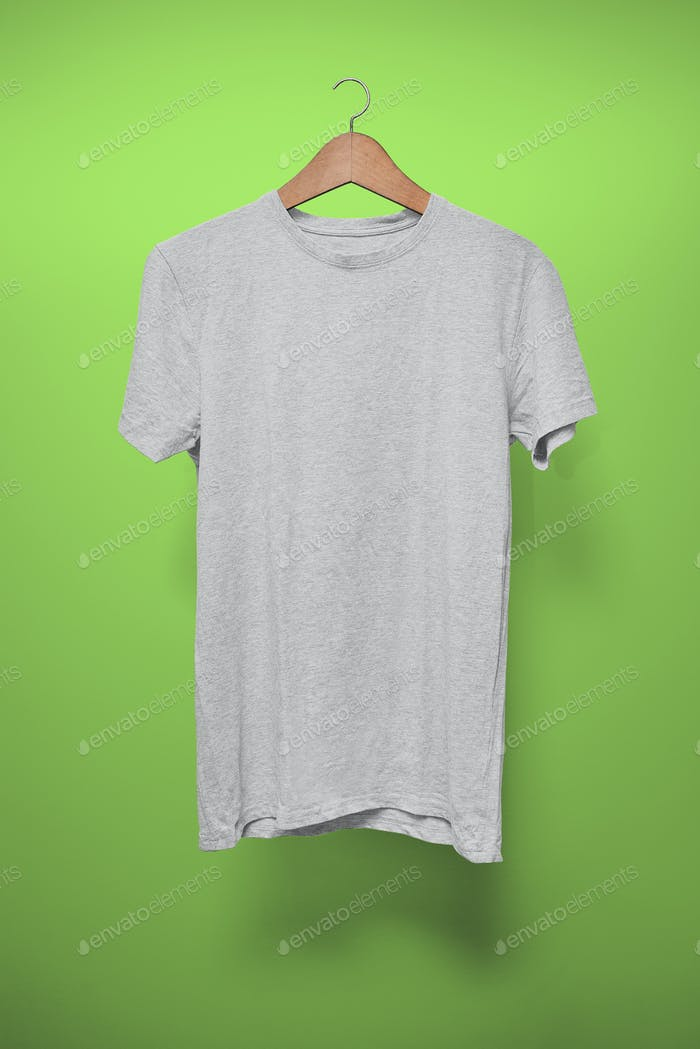 Grey T-Shirt on a hanger against a green background