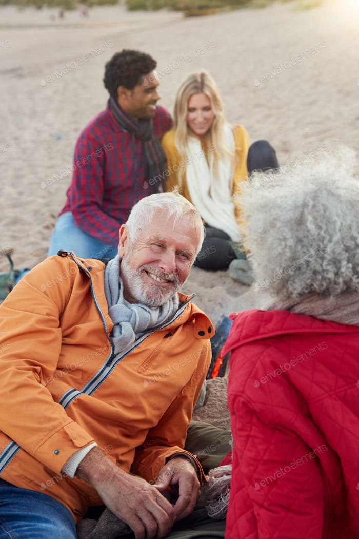 Loving Senior Couple Relaxing By Fire With Adult Offspring On Winter Beach Vacation