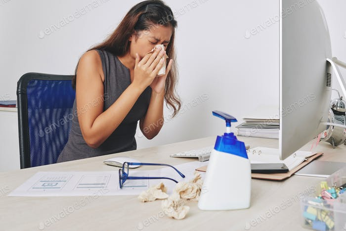 Sneezing businesswoman