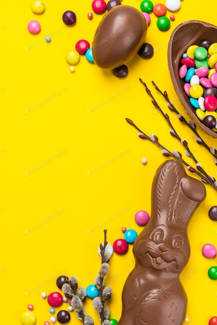 Easter Background. Chocolate Rabbit and Eggs with Colorful Candy. Copy Space on Flat Lay Design