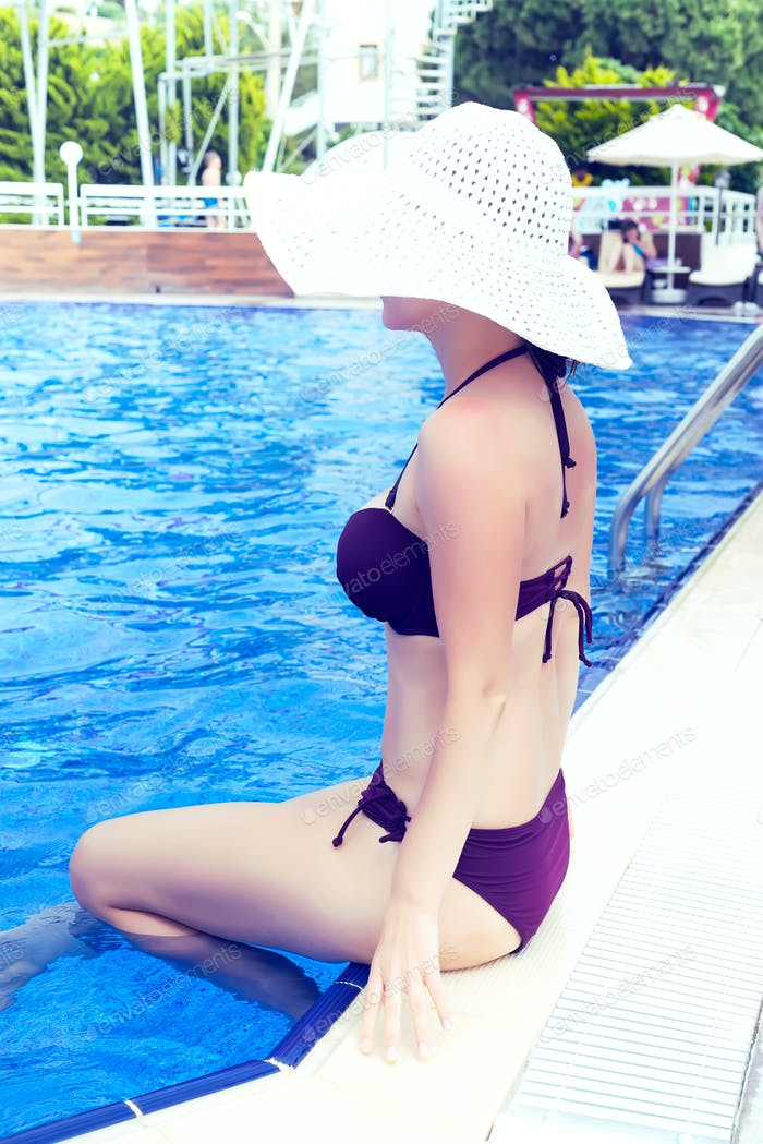 Beautiful woman in white hat and sunbathing on the pool blue water. Summer background