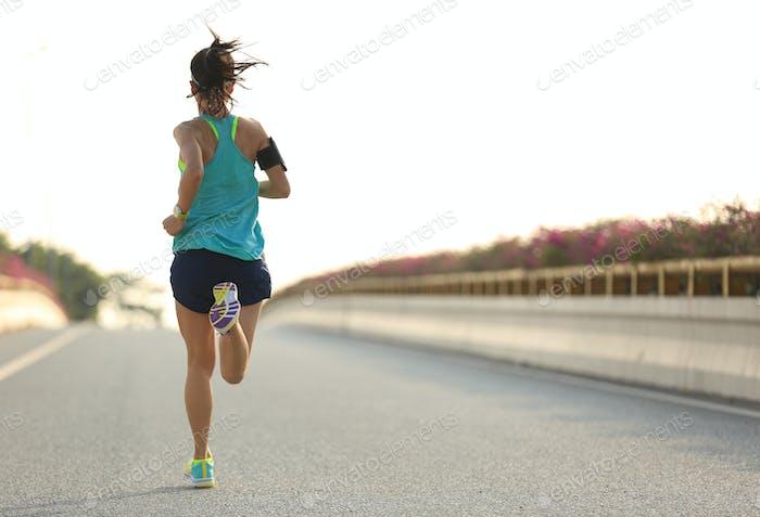 Fitness woman running on city street