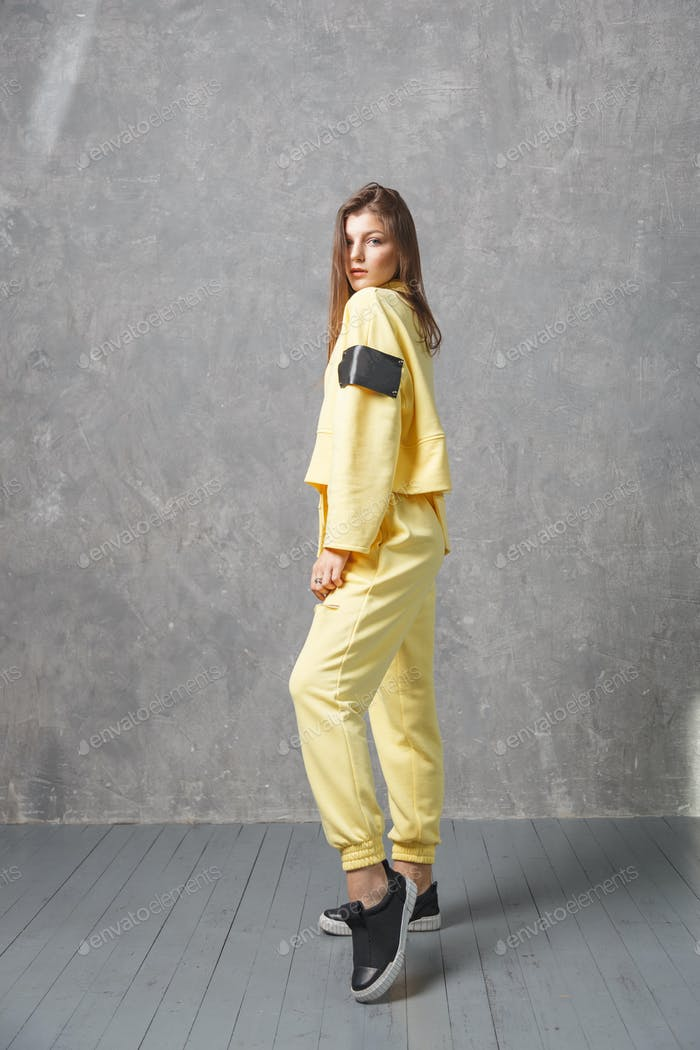 Young woman in yellow sportswear, pants and sweatshirt