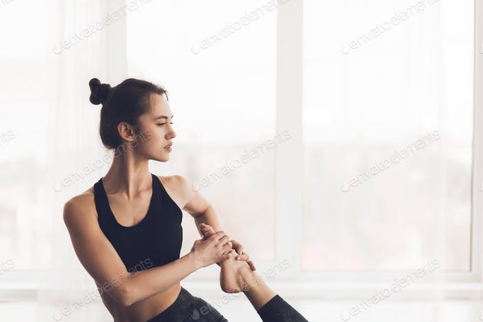 Sporty young woman stretching on yoga mat