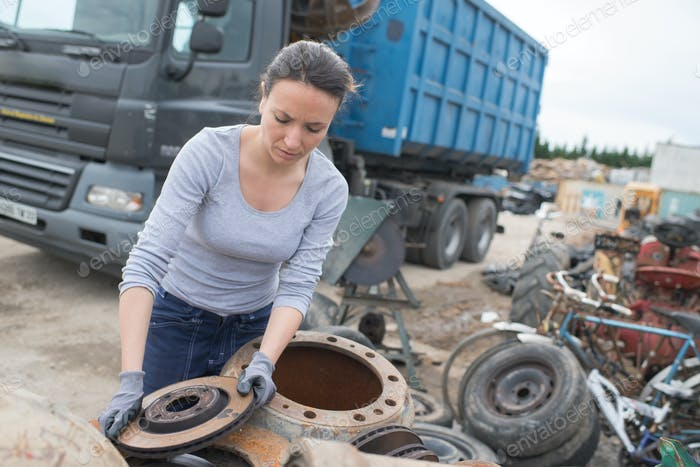 woman mechanic picking axle in car scrap yard