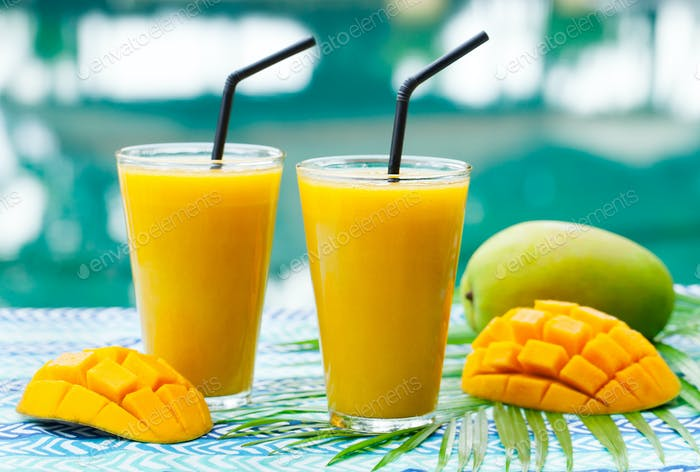 Fresh Tropical Fruit Smoothie Mango Juice and Fresh Mango on a Outdoor Tropical Background.