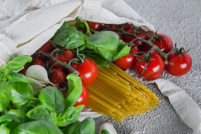 Reusable bag with groceries. Fresh basil, tomatoes cherry, garlic in fabric bag on table.
