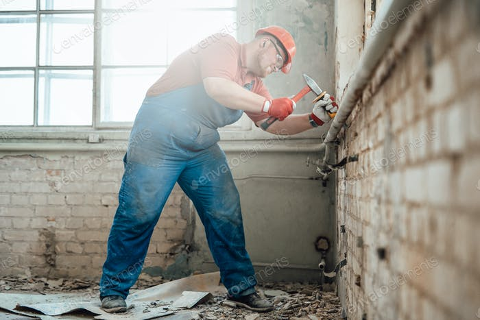 Fat builder on a construction site working on a brick wall with a hammer