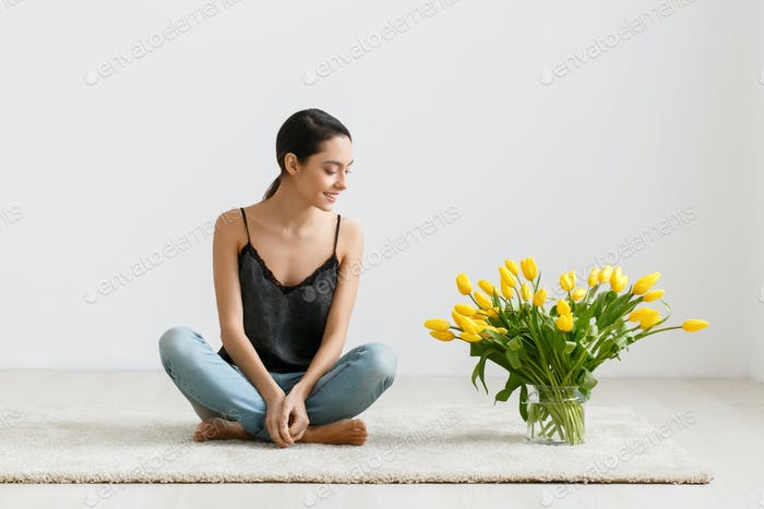 Woman with tulips. Young brunette girl with yellow flowers tulip natural portrait lifestyle.