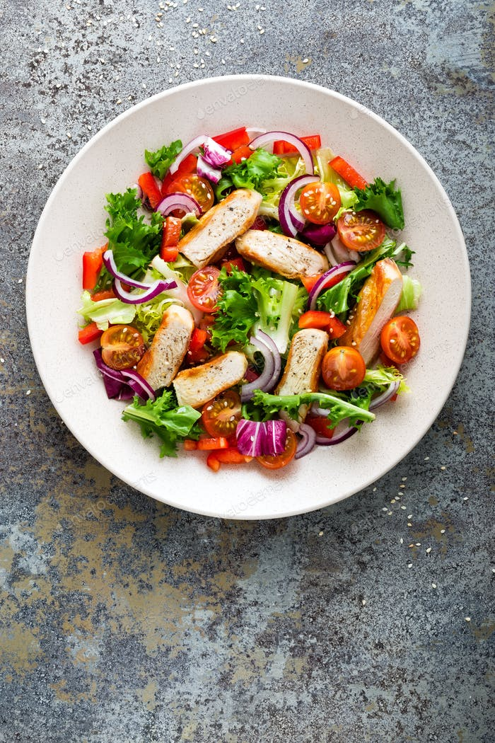 Healthy vegetable salad with grilled chicken breast, fresh lettuce, cherry tomatoes