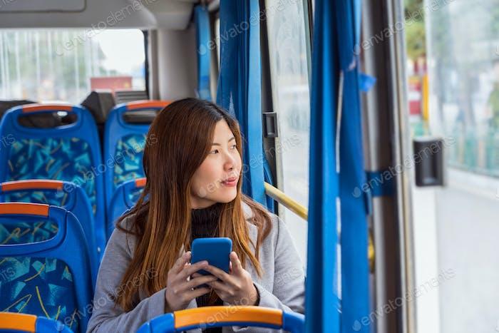 Азиатская женщина сидит в автобусе и использует мобильный телефон при путешествии по древней Дюкецзун