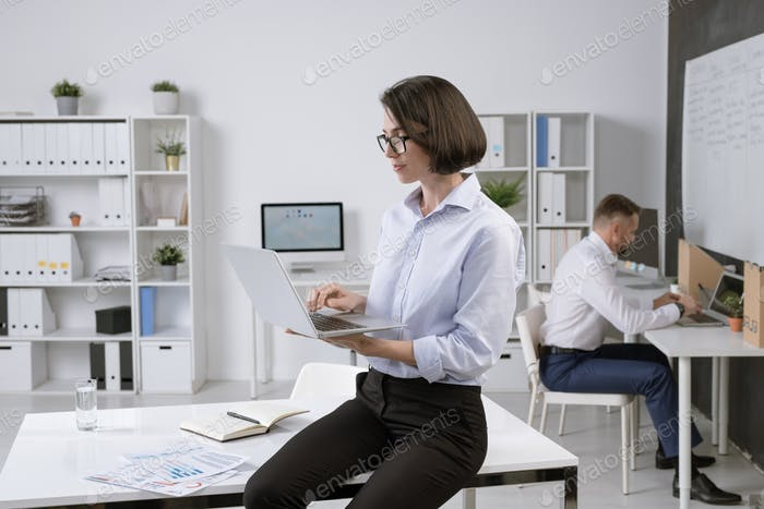 Pretty elegant businesswoman with laptop sitting on desk and surfing in the net