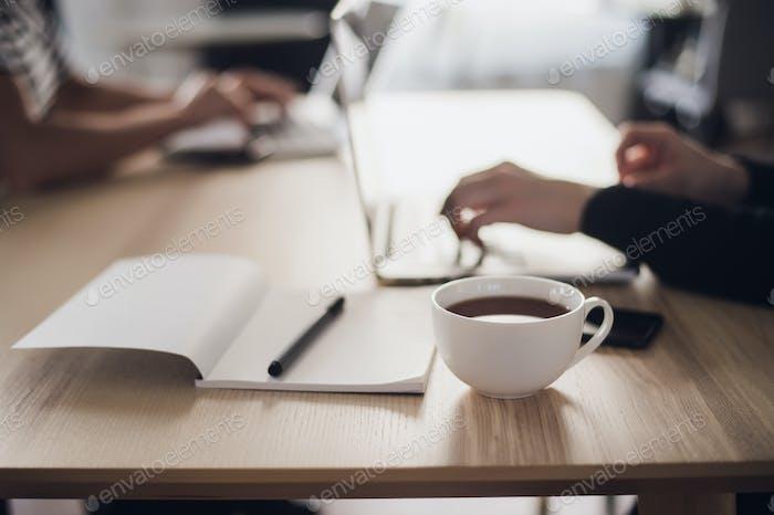 Schuss von den Händen einer Frau, die auf einer Laptop-Tastatur tippt, mit einer Tasse heißen Kaffee in der Nähe.