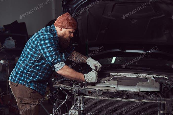 Bartmechaniker in einer Uniform gekleidet, stehend mit gekreuzten Armen gegen ein Auto in der Garage.
