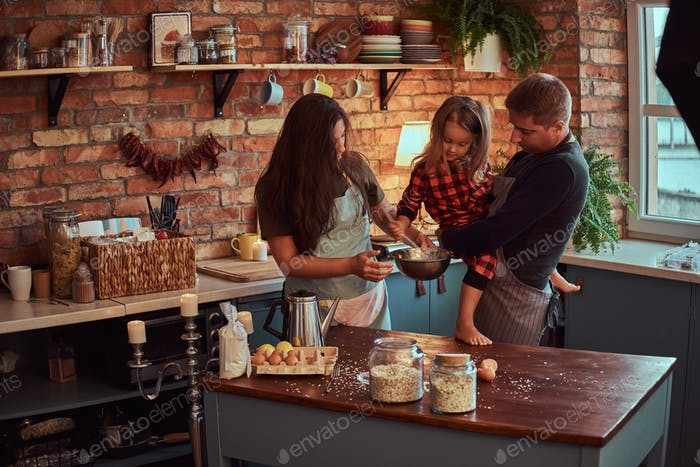 Mom dad and little daughter together cooking breakfast in loft style kitchen.