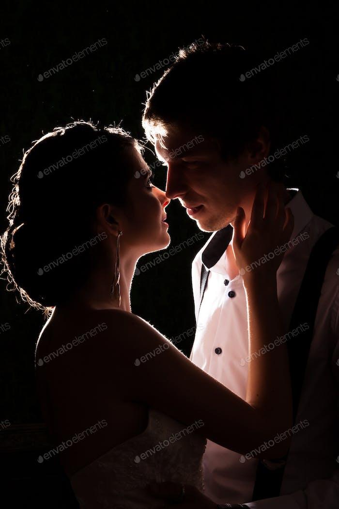 Gorgeous bride and groom together backlit