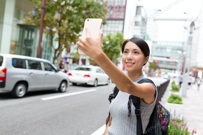 Woman taking selfie by cellphone in Fukuoka