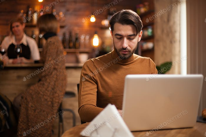 Young entrepreneur working on his laptop in a coffee shop