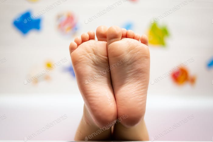 Baby im Badezimmer. Detail der niedlichen nassen Füße mit warmem Wasser bedeckt.