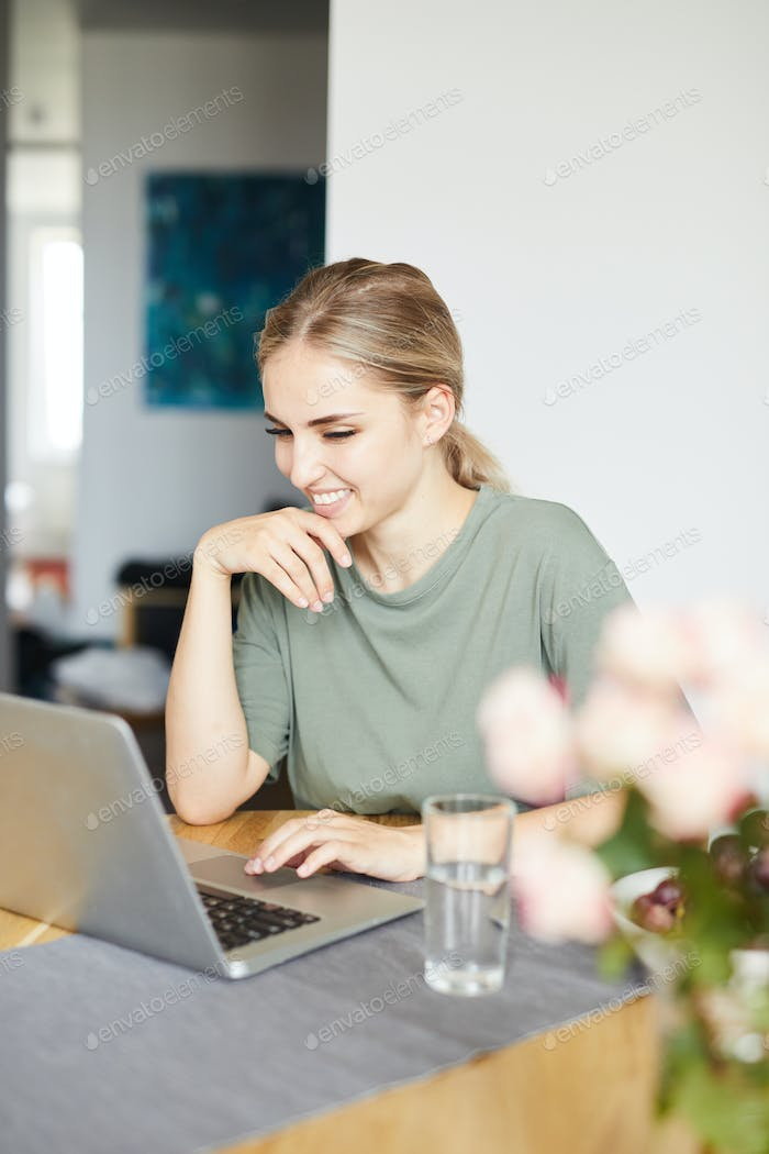 Happy young woman communicating through video-chat