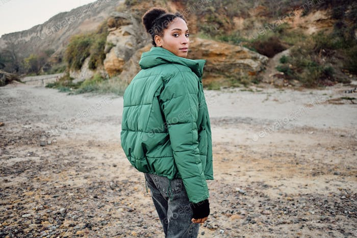 Beautiful African American girl in stylish down jacket dreamily looking in camera from back outdoor
