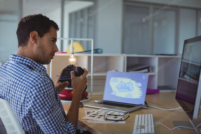 Photographer holding camera while sitting in creative office