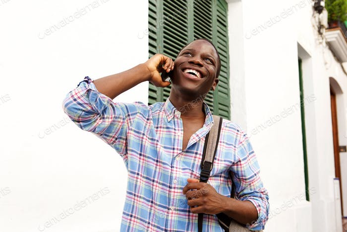cheerful young african man walking outside and talking on cell phone