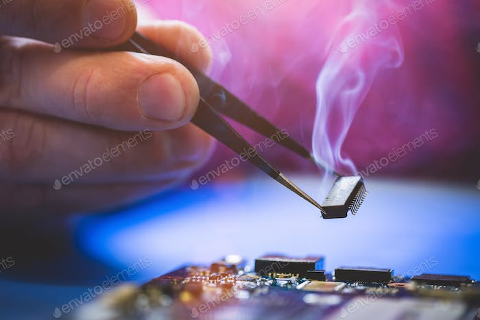 Man holding chip over the computer CPU board.