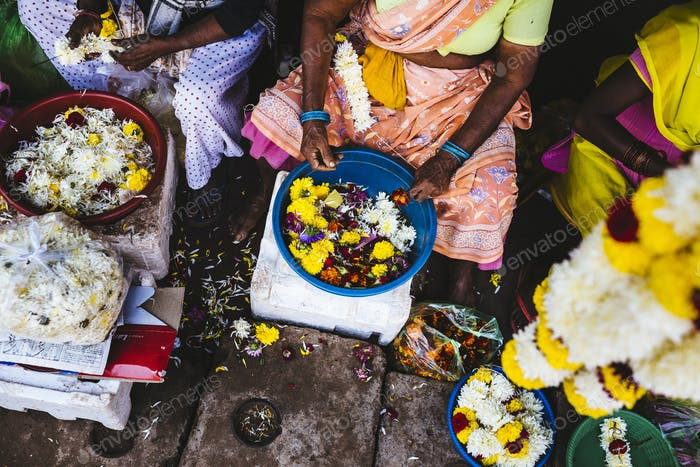 High angle close up of women lacing flowers on strings at a market.