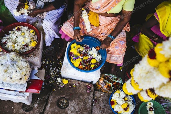 Hoher Winkel Nahaufnahme von Frauen Schnürung Blumen auf Saiten auf einem Markt.