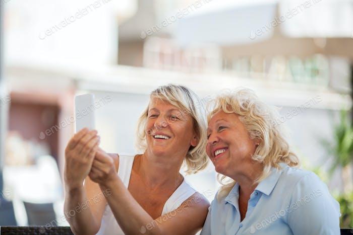 Happy senior women making mobile selfie