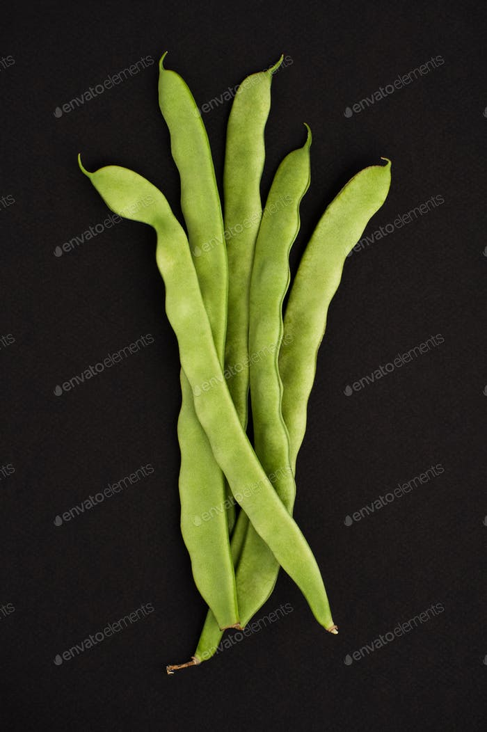 String of young beans on a black textured background.