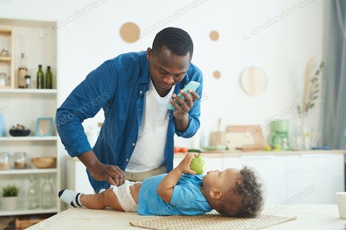 African-American Man Changing Diaper